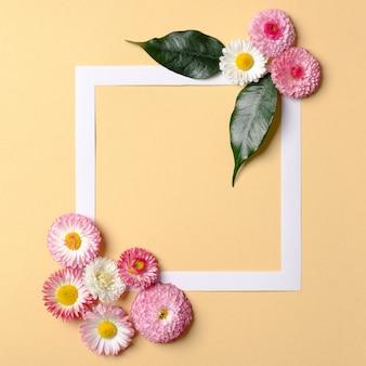 Creatieve plat lag samenstelling. vierkant frame met bloemen op pastel gele achtergrond. lente aard concept, minimaal ontwerp. bovenaanzicht, overhead.