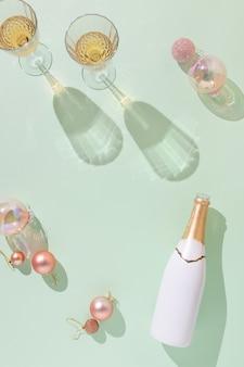 Creatieve plat leggen met witte en gouden champagnefles en kerstversiering tegen mintgroen oppervlak