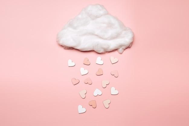 Creatieve plat leggen van objecten in de vorm van een hart die uit de wolk op pastel achtergrond vallen. liefde concept