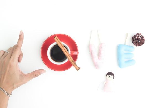 Creatieve plat leggen van woord liefde met de hand, kopje koffie en genaaid kussen