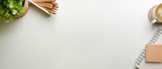 Creatieve plat leggen werkruimte met briefpapier koffiekopje plant pot en kopie ruimte op wit bureau