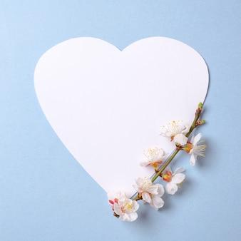 Creatieve platleg-compositie: hartvormig papier en bloeiende sakura-tak