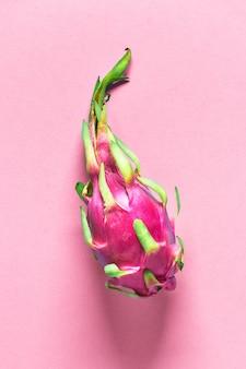 Creatieve platte lay-out met verse biologische roze, witte en groene dragonfruit op roze papieren oppervlak