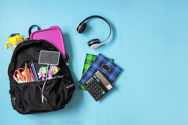 Creatieve platte schooltas met schoolbenodigdheden op blauwe achtergrond voor terug naar school concept