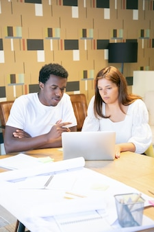 Creatieve professionals werken samen aan een ontwerpproject op laptop, zitten aan tafel en praten