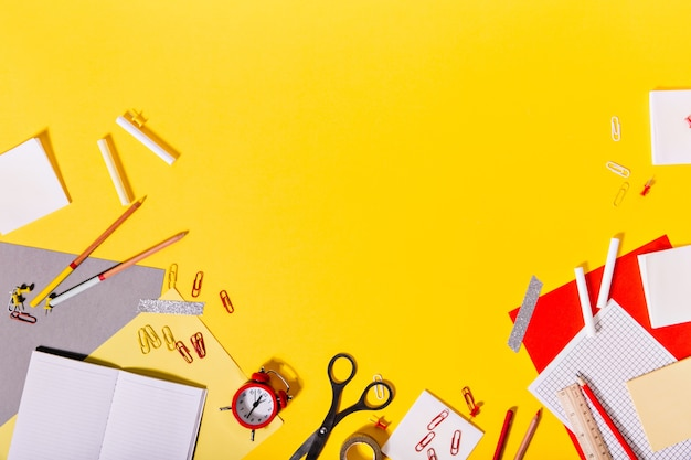 Creatieve puinhoop van kleurrijke schoolbenodigdheden op bureau.