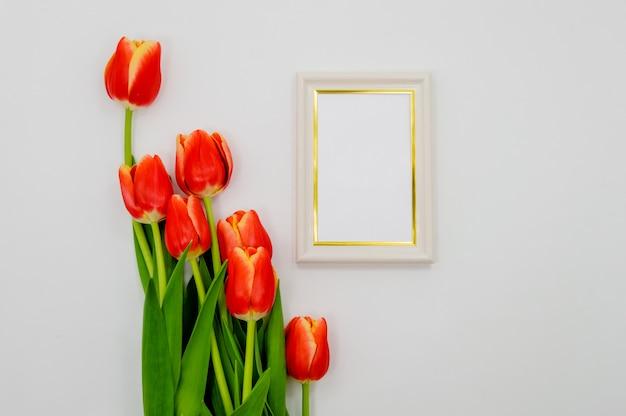 Creatieve samenstelling met fotolijst mockup, rode tulpen op abstracte achtergrond.