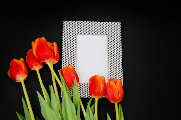 Creatieve samenstelling met fotolijst mockup, rode tulpen