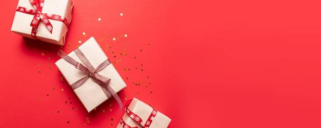 Creatieve samenstelling met rode huidige doos, ribons, rode gouden grote en kleine ballen, vakantiedecoratie op rood. creatieve compositie voor verjaardag, kerstmis, nieuwjaar