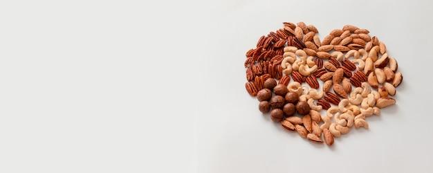 Creatieve samenstelling van diverse walnoot pecannoten, macadamis, paranoot, cashewnoten, amandelen op een grijze achtergrond. meng noten hartvorm. dieet, goed evenwichtig voedingsconcept