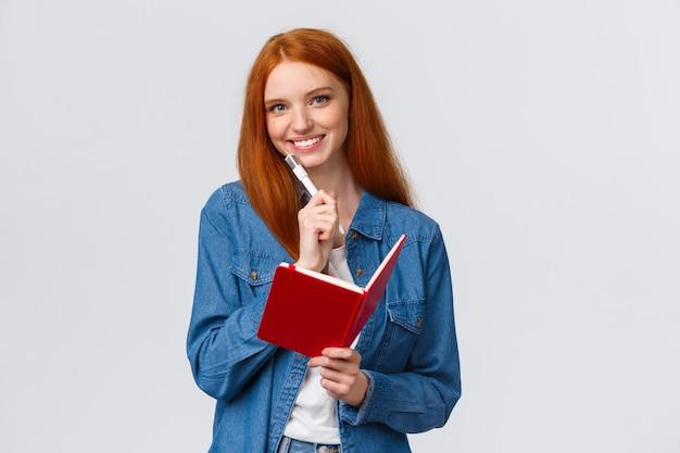 Creatieve schattige goed uitziende roodharige vrouwelijke student, tiener in casual outfit, pen vasthouden en camera glimlachen, notities maken in notitieblok, dagboek schrijven, schema opstellen dat wit staat