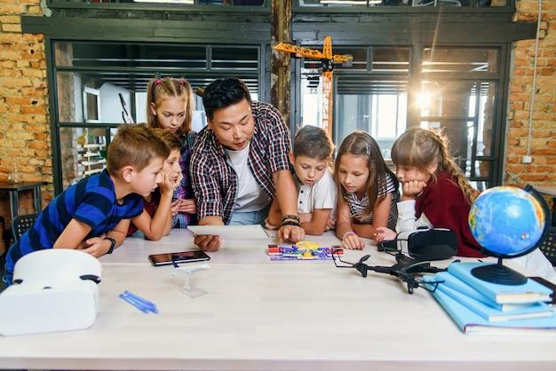 Creatieve schoolkinderen met jonge aziatische leraar studeren een elektronische constructor met ventilator en zetten zaklamp aan. school.