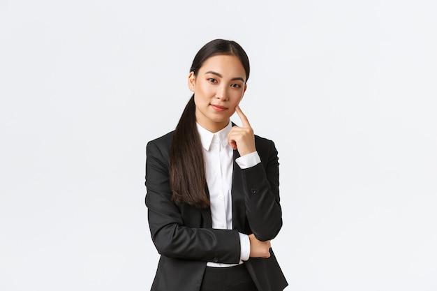 Creatieve slimme aziatische vrouwelijke manager, verkoopster in pak glimlachend sluw en kijkend naar de camera, hebben een plan, denken, hebben een uitstekend idee, staan tevreden op een witte achtergrond