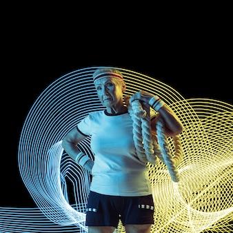 Creatieve sport op donkere neon verlichte lijnachtergrond. fitness, vrouwelijke atleet training in actie en beweging op kleurrijke golven. concept van hobby, gezonde levensstijl, actie, beweging, moderne stijl.