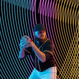 Creatieve sport op donkere neon verlichte lijnachtergrond. honkbalspeler training in actie en beweging op kleurrijke golven. concept van hobby, gezonde levensstijl, jeugd, actie, beweging, moderne stijl.