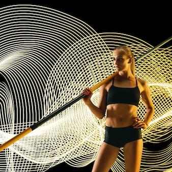 Creatieve sport op donkere neon verlichte lijnachtergrond. professionele polsstokhoogspringer training in actie en beweging op kleurrijke golven. concept van hobby, gezonde levensstijl, jeugd, beweging, moderne stijl.