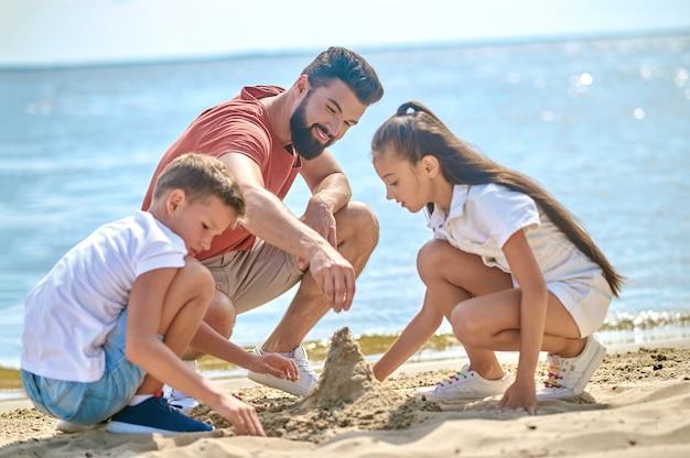 Creatieve stemming. een vader met kinderen die zandkastelen maken