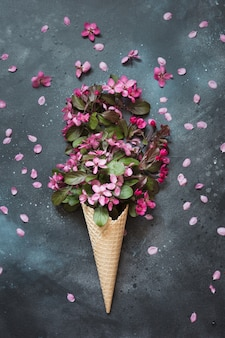 Creatieve stilleven van roze lentebloem in wafel ijsje op vintage tafel.