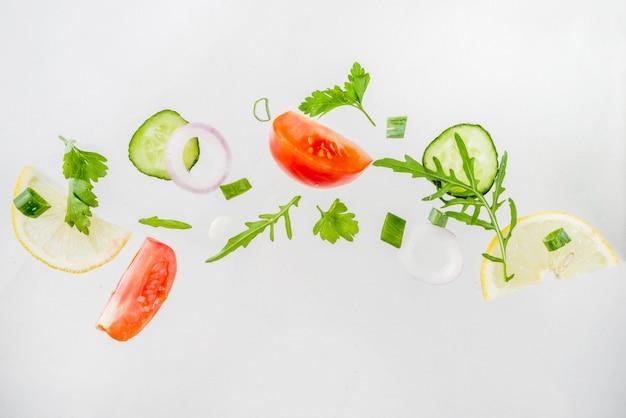 Creatieve tafel, lay-out, concept van verse gezonde voeding van salade, verse rauwe groenten tomaten peterselie uien komkommers groenen, eenvoudig patroon op witte tafel