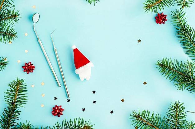 Creatieve tandheelkundige kerst en nieuwjaar. spiegel, sonde en stuk speelgoed tand in kerstmuts