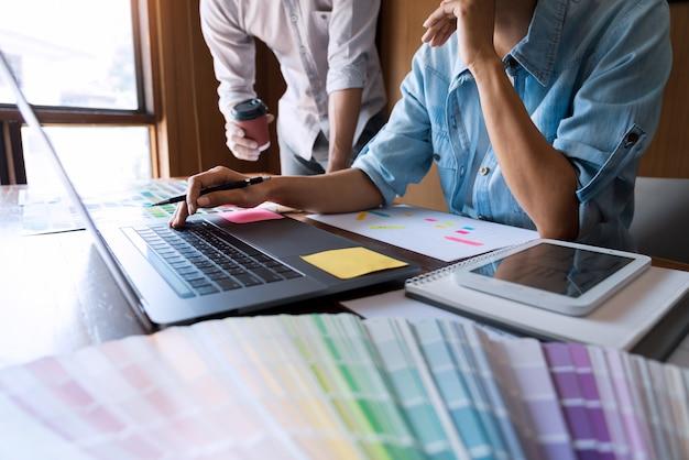 Creatieve teamontwerper die voorbeelden kiest met ui / ux die zich op schetsindeling ontwikkelen
