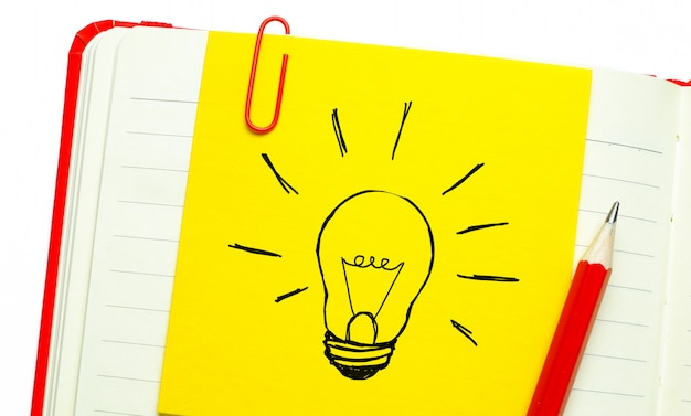 Creatieve tekening van een gloeilamp op een gele sticker bevestigd met een paperclip op een schoon vel open notitieblok. het concept van nieuwe ideeën, innovaties, oplossingen voor problemen.