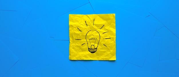 Creatieve tekening van een gloeilamp op een gele sticker