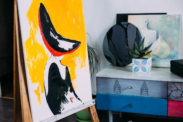 Creatieve thuisstudio-ezel met begonnen schilderpapier, schilderbenodigdheden