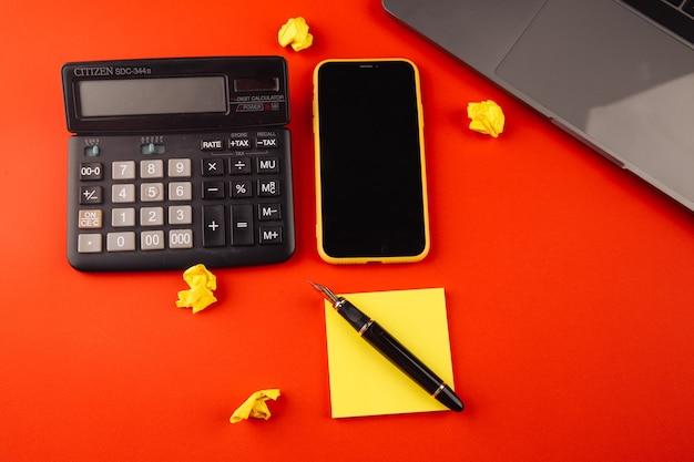 Creatieve thuiswerkplek met zwarte pen, clcok en gele notitie op rood