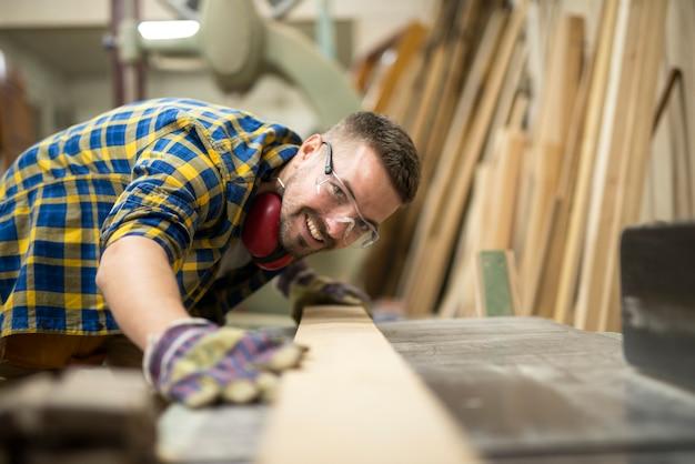 Creatieve timmerman die de gladheid van houtmateriaal controleert