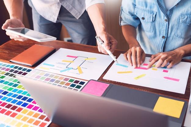 Creatieve ui-ontwerper teamwerk vergadering planning ontwerpen draadframe lay-out applicatie-ontwikkeling op smartphonescherm voor web mobiele telefoontechnologie.