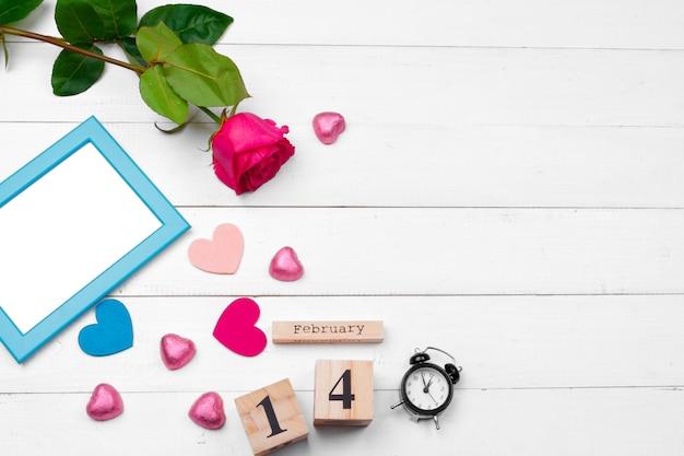 Creatieve valentine day-romantische samenstellingsvlakte legt hoogste van de de vakantieviering van de meningsliefde rode het hartkalender datum witte houten achtergrond