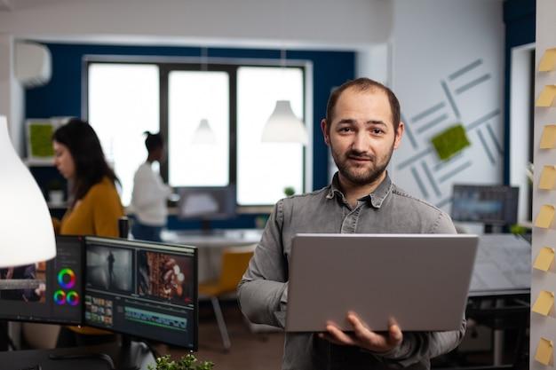 Creatieve video-editor werknemer staat voor camera