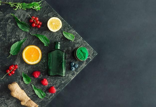 Creatieve voedsellay-out met fruit, groenten en bladeren op donkere stenen tafelmuur. minimaal gezond drankconcept. plat leggen.