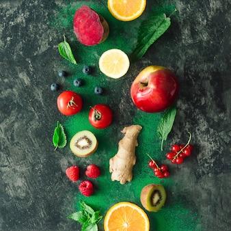 Creatieve voedsellay-out met fruit, groenten en bladeren op donkere stenen tafelmuur. minimaal gezond voedselconcept. plat leggen.