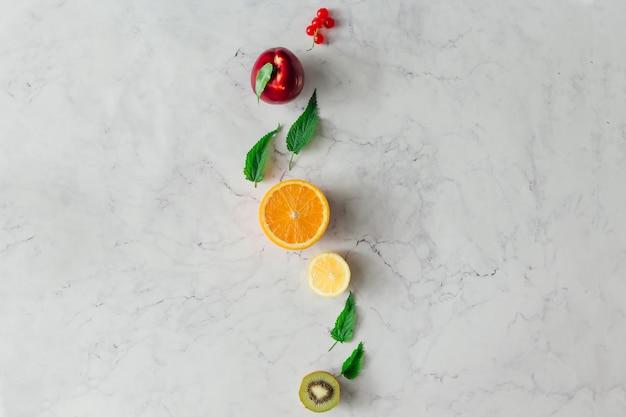 Creatieve voedsellay-out met fruit, groenten en bladeren op heldere marmeren tafelmuur. minimaal gezond voedselconcept. plat leggen.