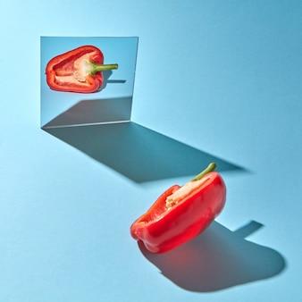 Creatieve voedselsamenstelling van peper en spiegel op een blauwe muur met harde schaduwen en exemplaarruimte. biologische groente