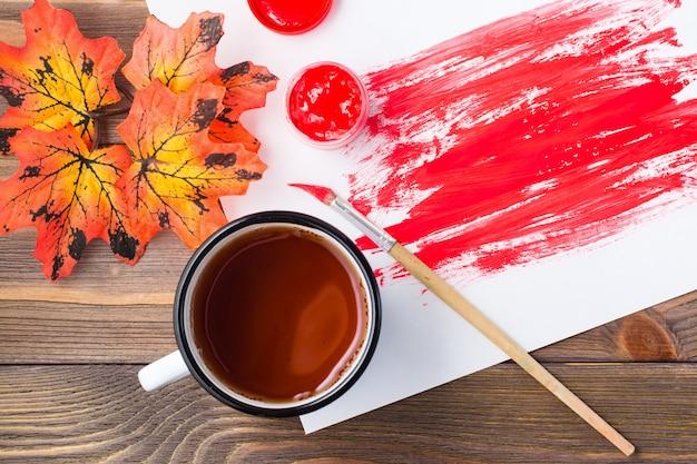 Creatieve vrijetijdsbesteding. abstract gouache-schilderij, thee in een mok en esdoornbladeren op houten