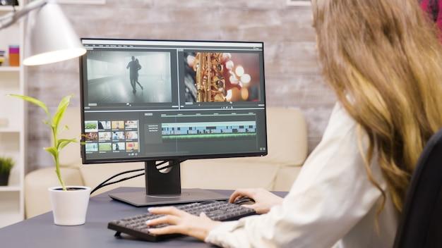 Creatieve vrouwelijke filmmaker bezig met postproductie van een film vanuit huis. vriend op de achtergrond.