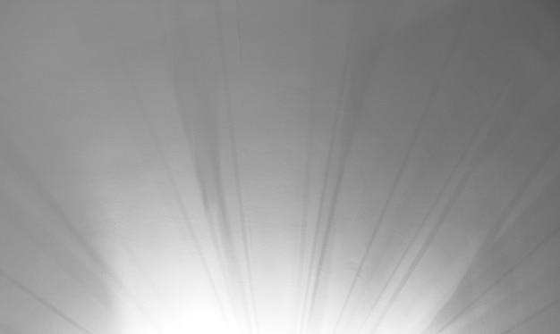 Creatieve wazig intreepupil achtergrond van divergerende banden van licht en schaduw op wit gepleisterd plafond. abstracte grijze en witte onscherpe achtergrond. kopieer ruimte voor tekst.