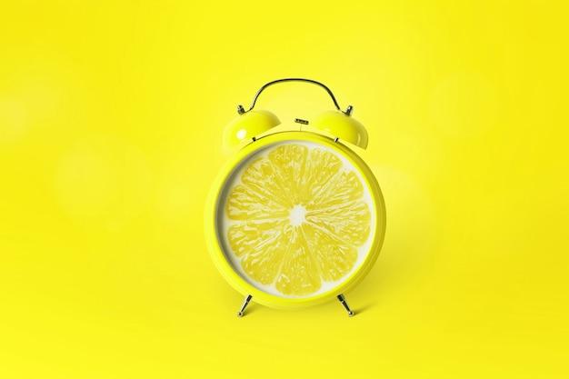 Creatieve wekker citrusvruchten citroen op gele achtergrond. tijd voor vitamine c, concept