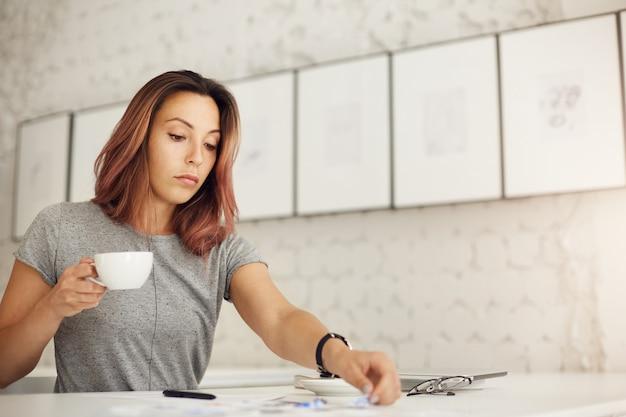 Creatieve werker die haar dagelijkse werk doet en koffie drinkt, rustend van haar overweldigende online leven.