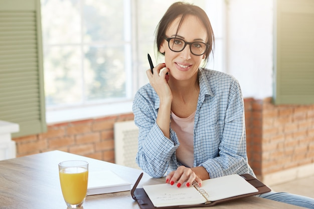 Creatieve werkneemster thuis, schrijft notities en plant haar schema, kijkt naar de camera. vrouw freelancer werkt op afstand, zit in de keuken.