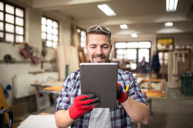 Creatieve werknemer timmerman op zoek naar nieuwe ideeën in werkplaats