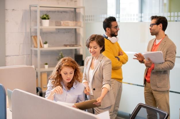 Creatieve werknemers die met gegevens in kantoor werken: productmanager die verkoopplan aanbiedt aan collega terwijl mannen papierwerk bespreken