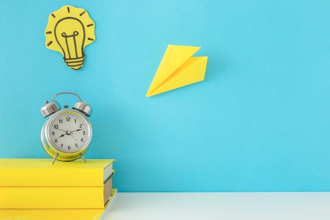 Creatieve werkplaats met gele notitieboekjes en wekker