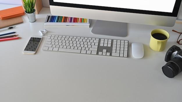 Creatieve werkruimte, koffiekopje en apparatuur op het bureau.