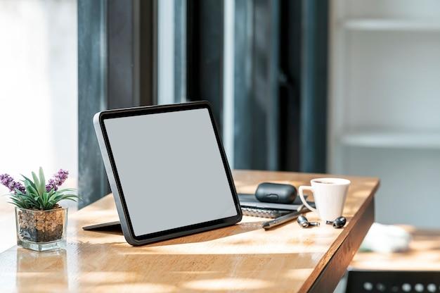 Creatieve werkruimte met tablet met leeg scherm op aanrechttafel in co-werkruimte