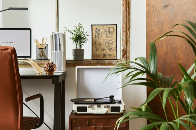 Creatieve werkruimtesamenstelling van modern mannelijk thuiskantoorinterieur met zwart industrieel bureau, bruinleren fauteuil, laptop, vintage platenspeler en stijlvolle persoonlijke accessoires. sjabloon.