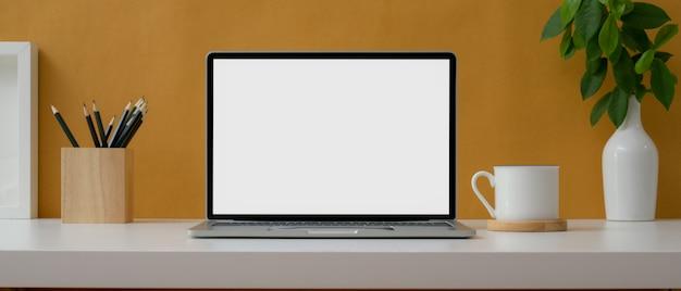 Creatieve werktafel met leeg scherm laptop, briefpapier, beker en decoraties op witte tafel met gele muur